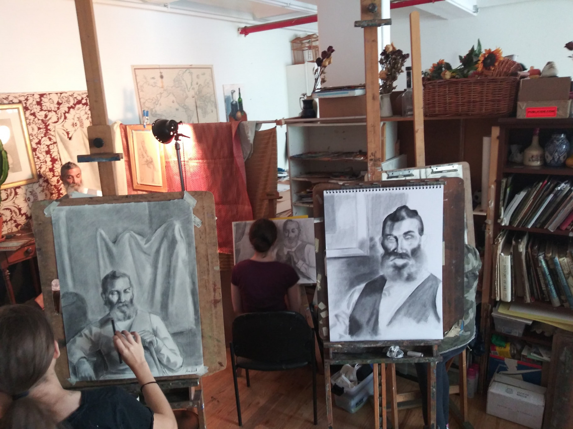 Teens drawing portrait from life during a master class.
